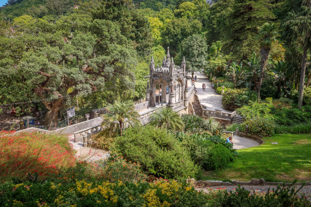 A path leads to an ornate gazebo surrounded by trees and other exotic plants
