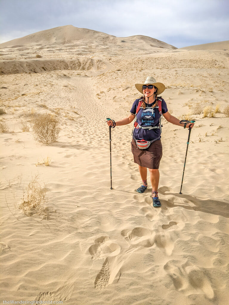 the author poses in front of the Kelso Dunes with hiking poles and broad straw hat