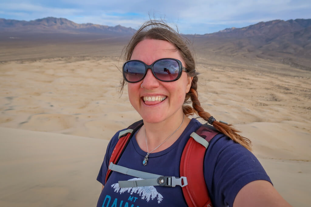 Selfie of the author at the top of the dunes. Her hair is whipping around in the wind and she has no hat.