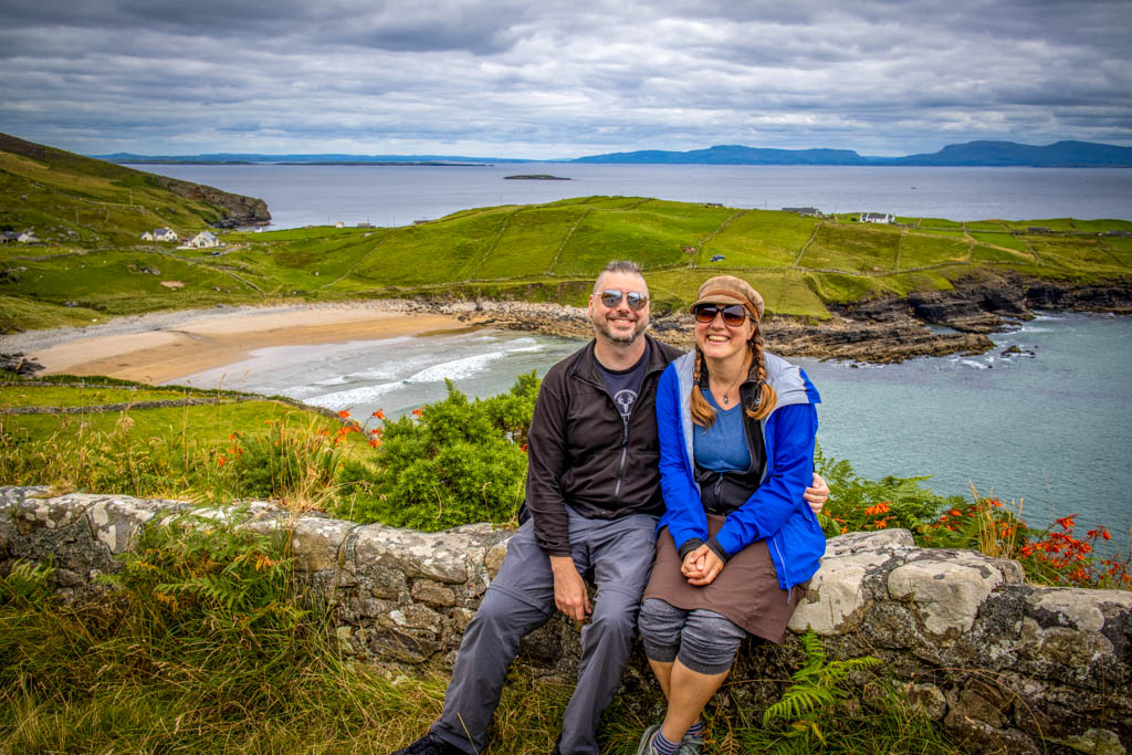 The author and her husband sit on stone wall with Muckross Head in the background on their Donegal day trip