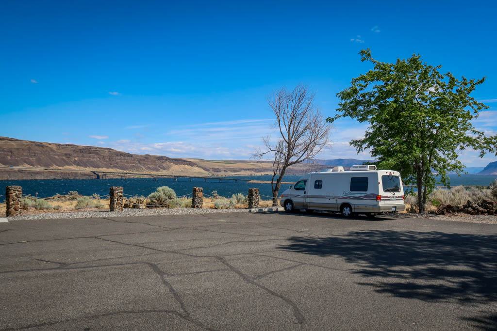 Winnebago Rialta parked near the edge of the enormous Columbia River with a view of Vantage Bridge
