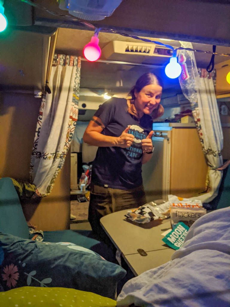 the author stands inside the Rialta motorhome near the back dinette seats and folding table