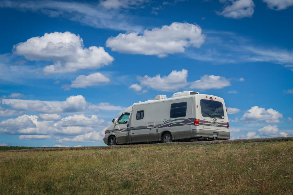 Appa parked under a blue sky with puffy white clouds in Yellowstone National Park