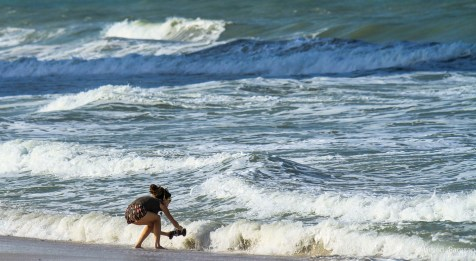 Lady taking pictures of the waves at Ajman Beach during the cold and windy weather in Sharjah.