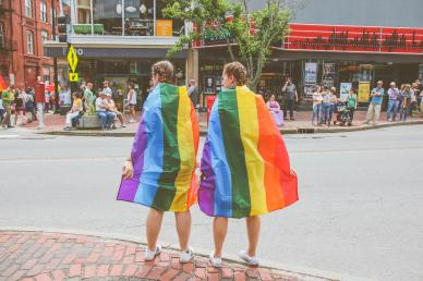 Photo of two women wearing LGBT pride flags around their shoulders.