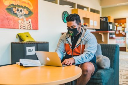Photo of a student with a mask on working on a laptop in the Student Equity Center