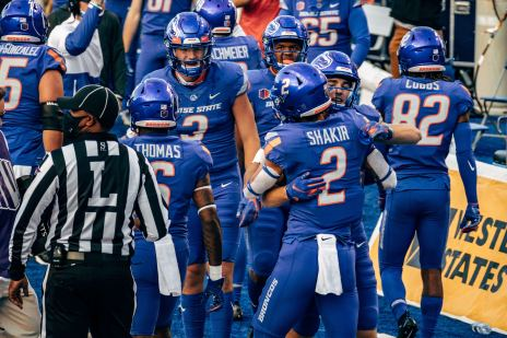 Boise State Bronco football players celebrating on the sidelines.