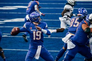 Boise State football player winds up to pass the football to another player.