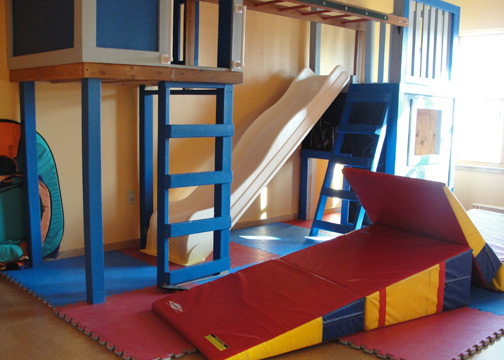 photo of the play room with climbing structure and tumbling mats.