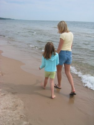 Danielle and her birth daughter, Alyssa, walk along the beach holding hands. Alyssa looks up at Danielle