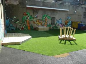 Children's play bridge with wooden deck and storage boxes on artificial turf
