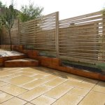 Rear garden makeover featuring Indian sandstone paving and ornamental timber screen