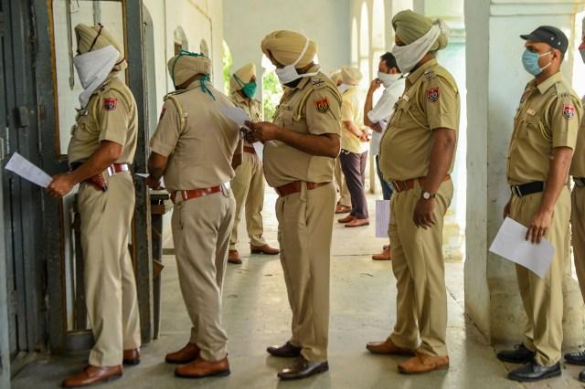 El personal de la Policía hace cola mientras espera a ser revisado por los trabajadores de la salud en un hospital en Amritsar el 22 de abril de 2020. (Foto de NARINDER NANU / AFP)