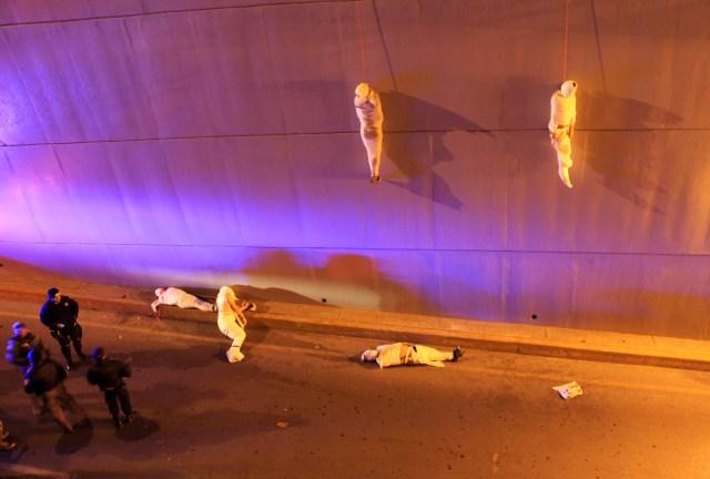 Los cuerpos envueltos de dos personas fallecidas cuelgan de un paso elevado mientras tres más yacen en el suelo en Saltillo, México, el 8 de marzo de 2013 (REUTERS/Stringer)