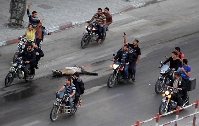 Palestinos viajan en motocicleta y arrastran el cuerpo de un hombre, sospechoso de trabajar para Israel, en la ciudad de Gaza, el 20 de noviembre de 2012 (REUTERS/Suhaib Salem)