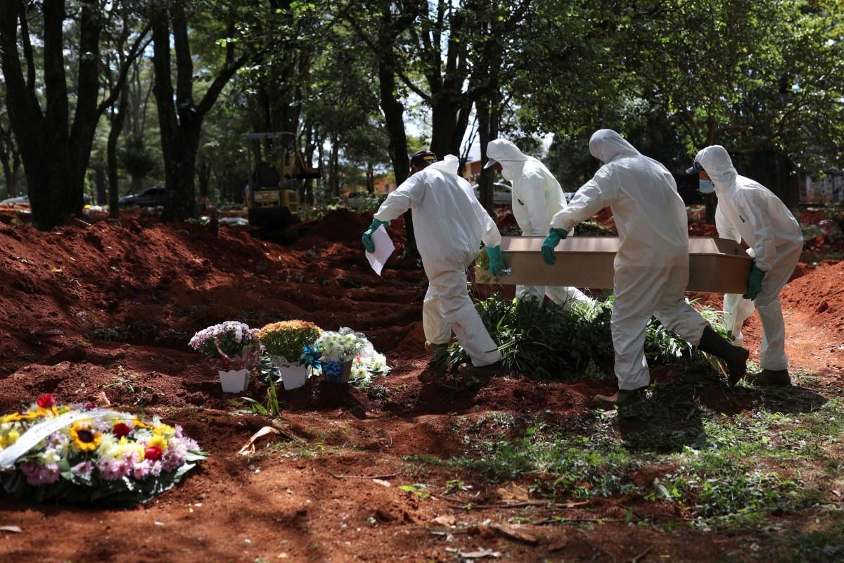 Los sepultureros con trajes protectores llevan el ataúd de una persona que murió por COVID-19, en el cementerio de Vila Formosa (Reuters)