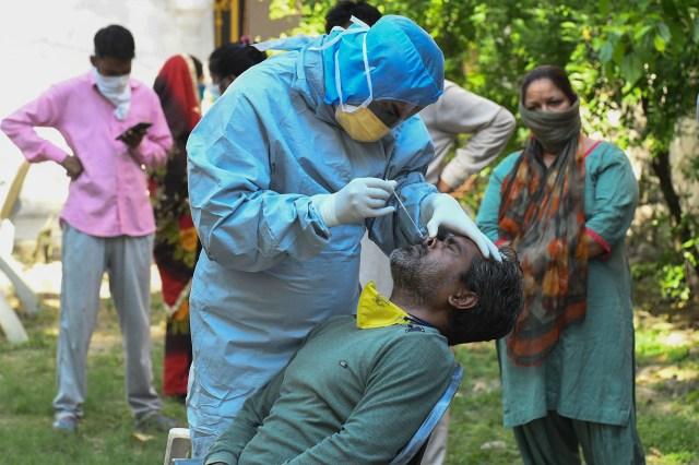Un médico toma una muestra de un hombre para una prueba COVID-19 en Amritsar el 23 de abril de 2020. (Foto de NARINDER NANU / AFP)