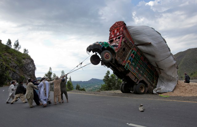 Un grupo de hombres utiliza sogas para tratar de aderezar un camión de suministros sobrecargado con paja de trigo, utilizado como alimento para animales, a lo largo de una carretera en Dargai, en el distrito de Malakand, a unos 165 km de la capital de Pakistán, Islamabad, el 13 de abril de 2012 (REUTERS/Mian Khursheed/File Photo)