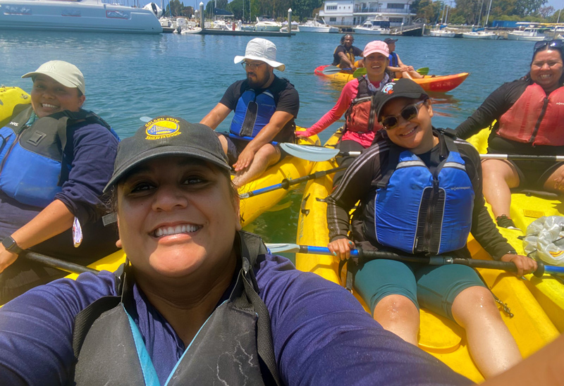 Staff smiling while out on the water in Marina del Rey during a kayaking trip.