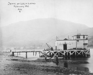 Scanned image of photograph of Arrochar Royal Navy Torpedo Testing Station and Range showing pier head building including part of the pier and a small crane from NW. Titled 'Jetty at Loch Long'. SC1064426 Copyright RCAHMS