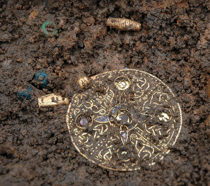 A circular pendant and gold and glass beads, coming from Grave 70 at Street House - a 7th-century cemetery near Loftus