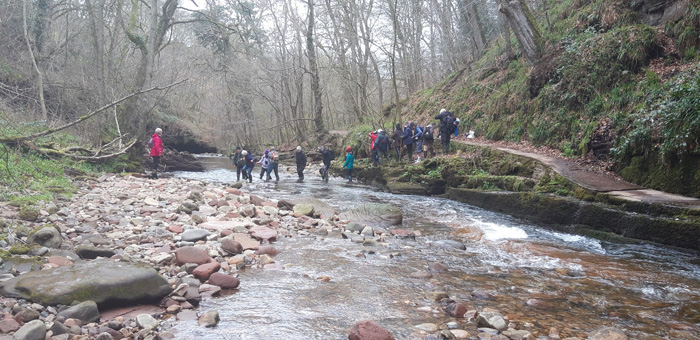 A modern group of visitors crossing the River Gelt to see the inscriptions