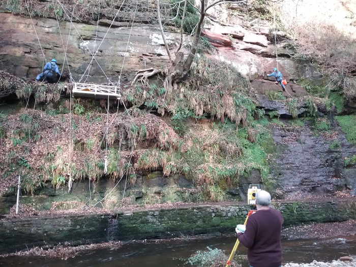 Researchers using ropes to access eroding Roman inscriptions on an ancient quarry wall in Cumbria