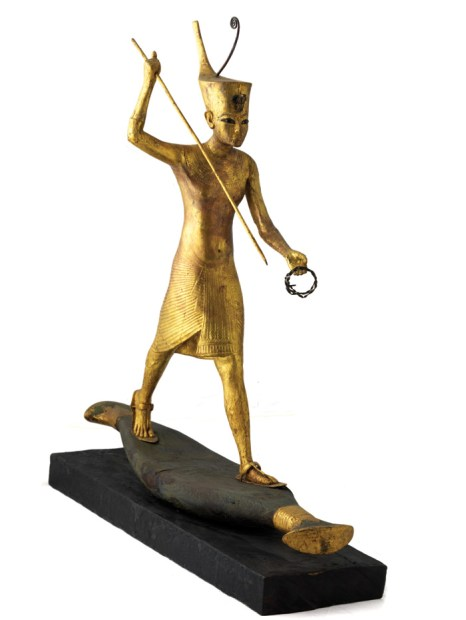 A gilded wooden figure showing Tutankhamun on a skiff, poised ready to strike with his harpoon