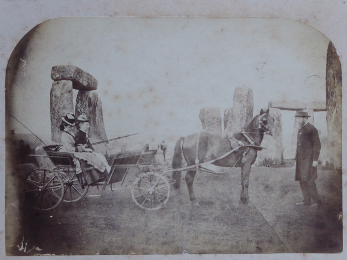 An old photograph of two women sat in a horse drawn carriage, with a man next to the horse