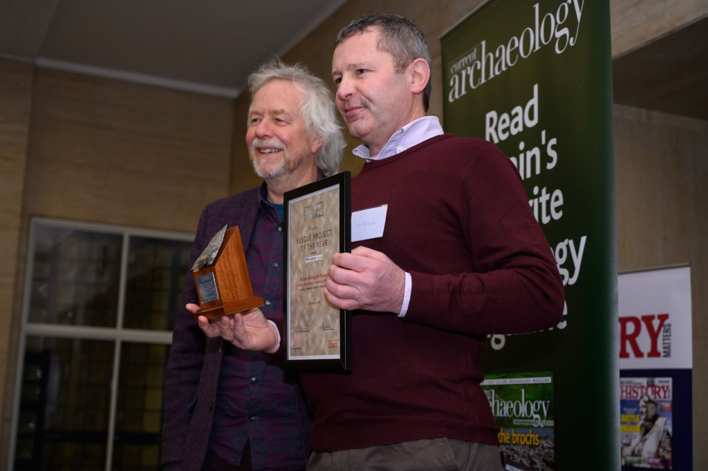 Julian Richards (left) presents the award for Rescue Project of the Year, which is collected by Jon Allison (right) at the Current Archaeology Awards. [Photo credit: Adam Stanford, Aerial-Cam]