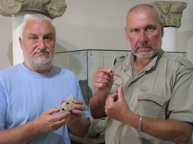 Bulgarian archaeologists Angel Konakliev (left) and Nikolay Ovcharov (right) showing some of the newest discoveries from the medieval city of Missionis / Krum's Fortress near Bulgaria's Targovishte: Konakliev holds a 5th-6th century AD clay lamp, and Ovcharov - a medieval fishing hook. Photo: Targovishte Municipality