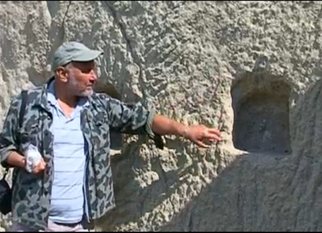 Archaeologist Nikolay Ovcharov shows rock niches that may have been used as altars in the Roman Era temple of the Thracian Horseman (Heros), the supreme deity of the Ancient Thracians. Photo: TV grabs from BNT