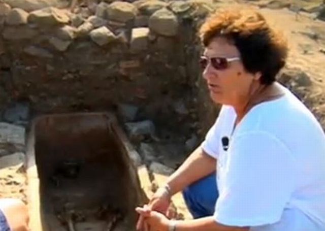 Archaeologist Krastina Panayotova is seen here on the side of the grave containing the ceramic sarcophagus. Photo: TV grab from BNT