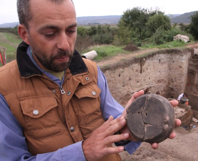 Archaeologist Alexander Chohadzhiev shows the lid of a prehistoric vessel found in the Chalcolithic settlement mound near Bulgaria's Petko Karavelovo, which was repaired in an interesting way back in the Copper Age. Photo: Borba daily