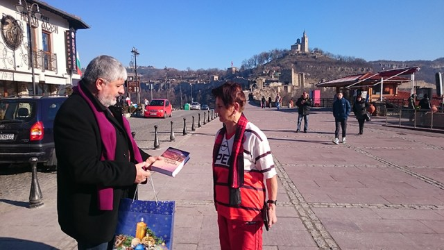 Ivan Tsarov (left), Director of the Veliko Tarnovo Regional Museum of HIstory, is pictured awarding 79-year-old Stefka Ognyanova, the first tourist to visit the Tsarevets Hill Fortress for 2016. The main entrance of the Tsarevets Architectural and Museum Preserve is visible in the background. Photo: Veliko Tarnovo Regional Museum of History