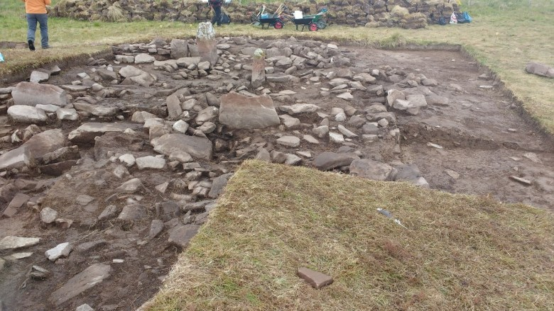 The two stones originally the only visible part of the strcuture before excavation. Also visible is one of the Bronze Age houses