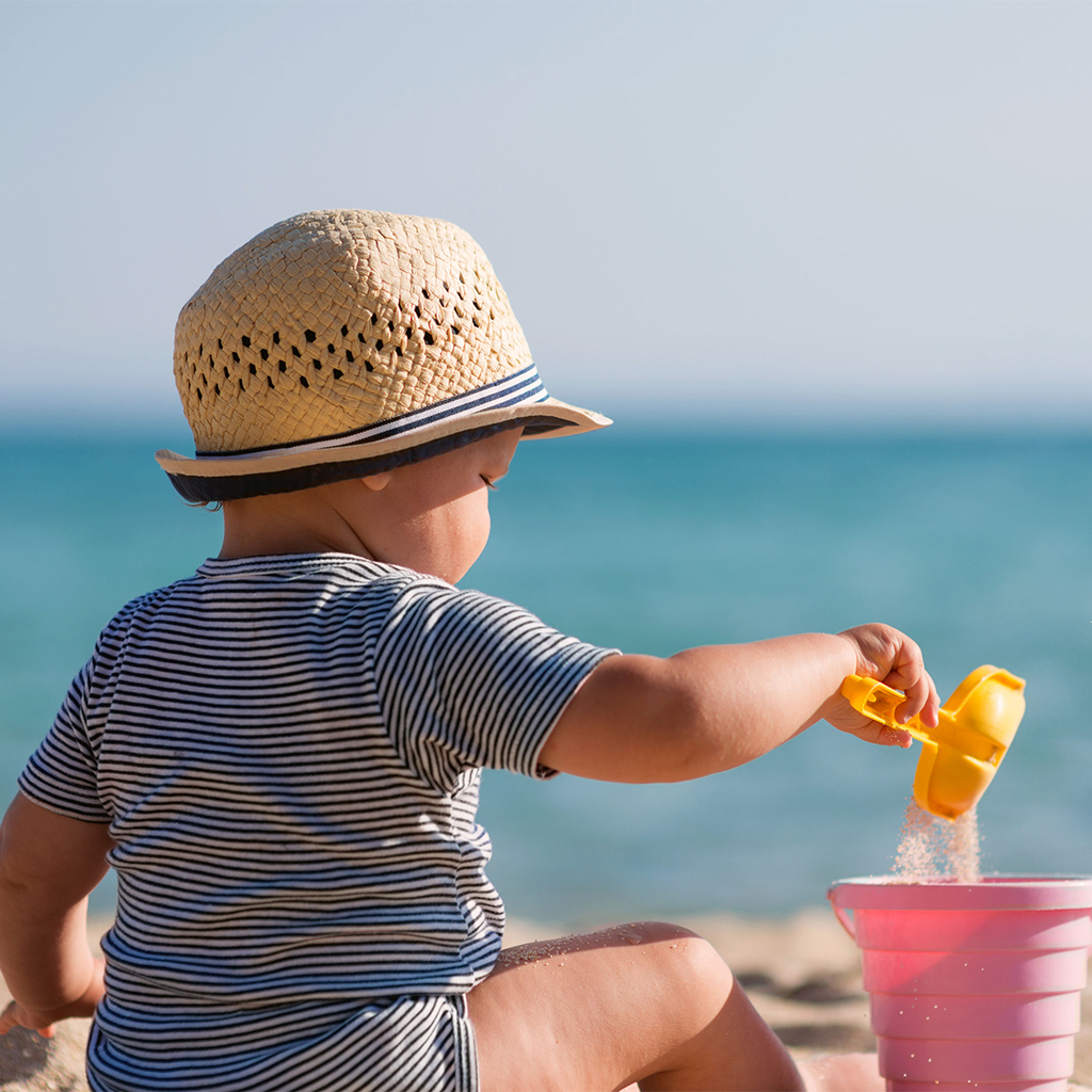 Infant playing with sand on beach
