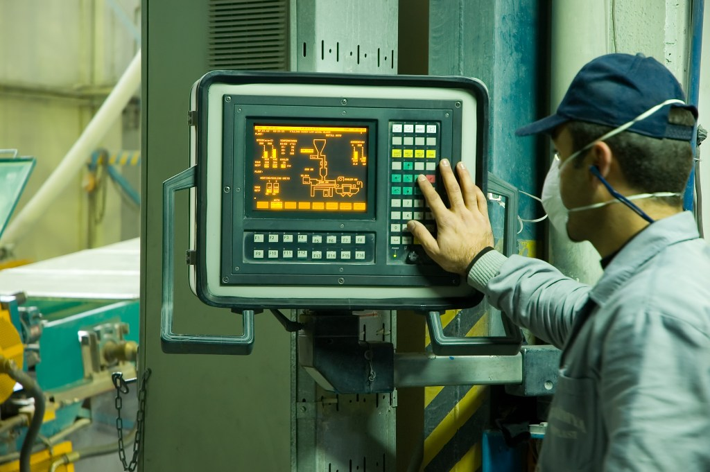 A worker touches a computer screen at a factory