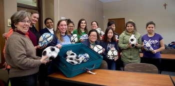 Members of the theology club deflate donated soccer balls to send with Bakdash on his trip to Jordan in March