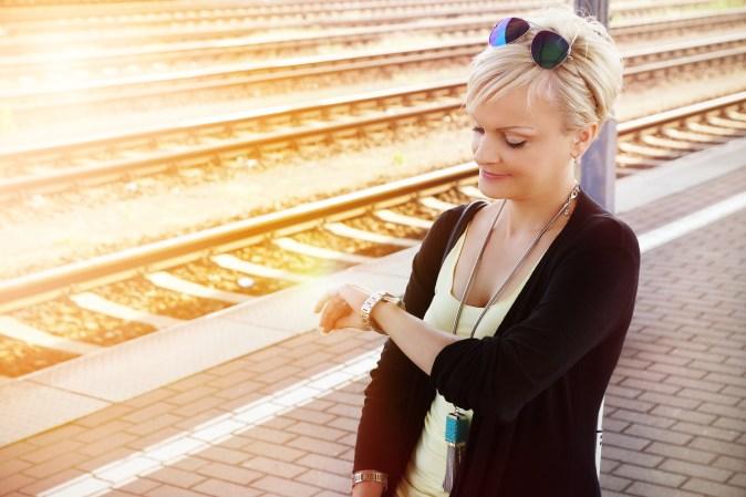 junge Frau wartet ungeduldig auf ihren Zug