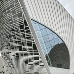 """The facades are entirely clad with ceramic elements. The glazed façade of the venue foyers called the """"Curved Galleries"""" are shaded on the exterior by white ceramic baguettes with a lens shaped profile"""