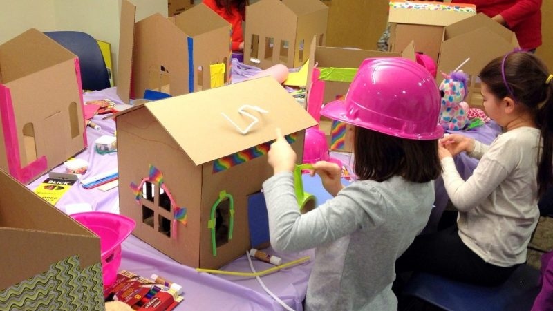 several children wearing pink hardhats engaged in an architecture building party