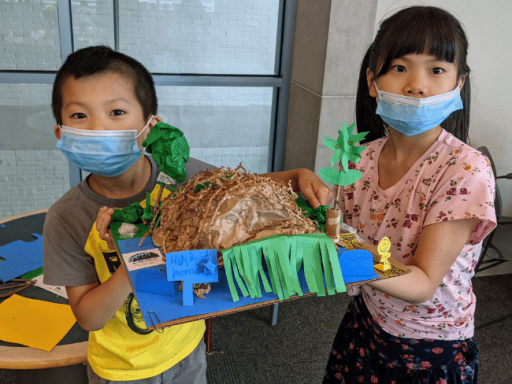 two siblings showing their muskrat lodge project produced using cardboard, construction paper and recycled materials.
