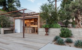 The steel trellis over the entrance to the pool house will provide shade when planted, clerestory windows let in light from above. The cabana and bar also features sliding barn doors, small kitchen, flush-mount cabinets, and exterior supply cabinet. The exterior is clad in corrugated steel and high fire rated cedar. To the right of the pool house is an intimate seating area that provides privacy and shade.