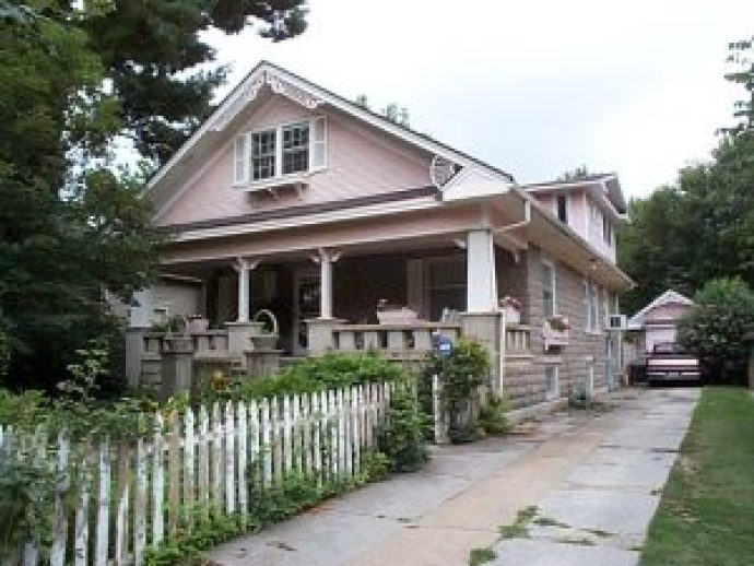 When built, this house Craftsman-style house possessed a rugged handsomeness characteristic of the Arts and Crafts era. The weighty front gable, masonry balustrade and rusticated block walls give this house a visual heft that no amount of pink paint, spindled fretwork and shutters can obscure.