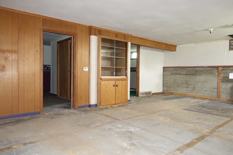 The living / dining room showing poured concrete slab after carpeting was removed. A wood paneling wainscot was removed from the lower section revealing the concrete foundation wall. The block portion of the wall above it still retains 1980's-era wallpaper.