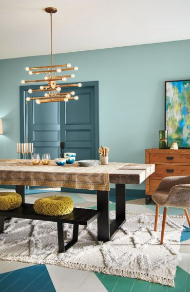 Soft aqua walls are layered with deep blue-green trim, modern furnishings and sparkling gold accents.