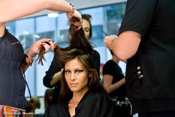 A modely gets her hair done backstage at Friedrich Gray