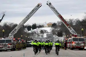 Bicycle police offices make their way to Arlington National Cemetery ahead of the hearse carrying Sicknick.
