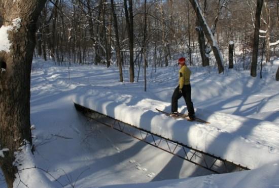 snowshoer walking on a bridge